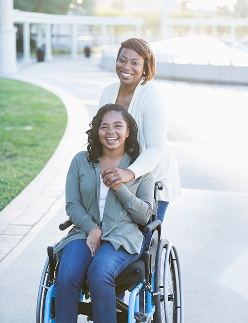 Image of a girl in a wheelchair and her mom with him